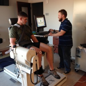 Grad student analyzing leg extension force of study subject using Biodex machine.