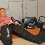 Research subject sitting on ground wearing two, black Normatek compression boots for therapy.