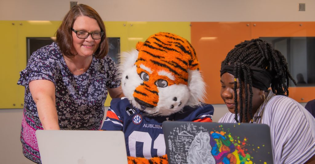 """Auburn's mascot """"Aubie"""" seated at a table with a laptop accompanied by a student also seated at a laptop; a staff member stands and addresses the student and mascot"""