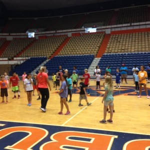 Elementary campers doing zumba in gym.