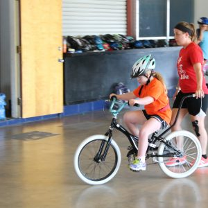girl riding bike with iCan Shine helper assisting