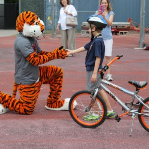 Aubie the tiger shaking hands with bike camper