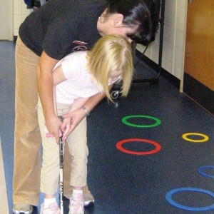 teacher helping student putt