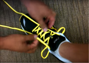 tie yellow laces on black athletic shoe