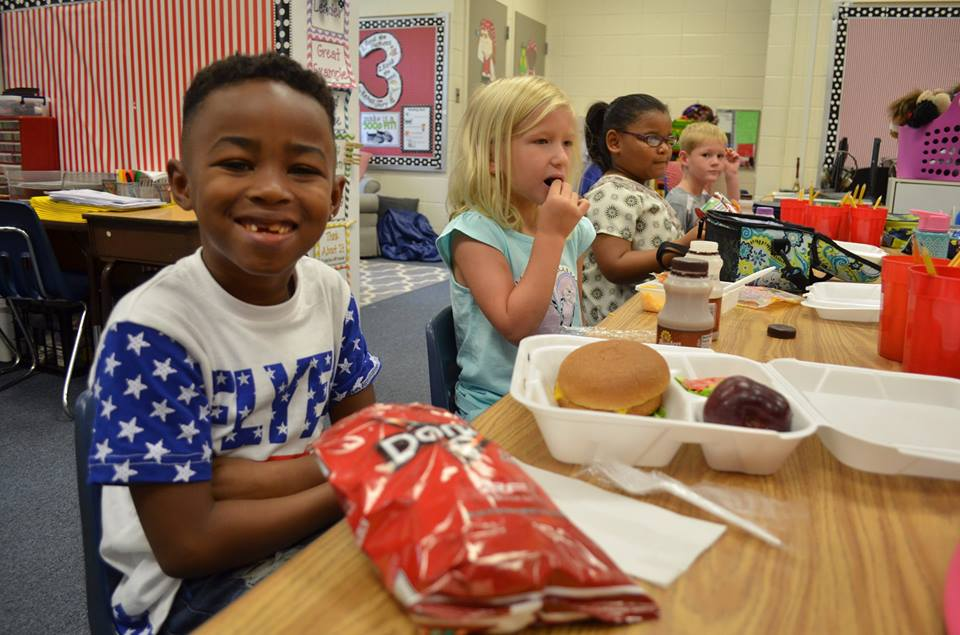 Seated students enjoy boxed lunches
