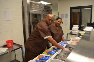 Lunchroom staff smile while assembling lunches for students