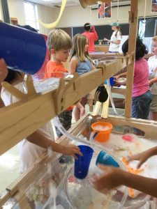 Children interact with water table, buckets, and bubbles