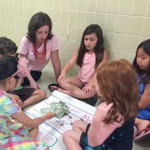 Children interact with an instructor in a money activity. Real money and a large notepad are used.