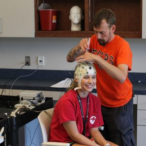 Student wears cap for testing in KINE lab