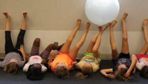 Girls participate in group exercise with ball