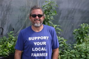 "O Grows executive director Sean Forbes, Ph.D. He is wearing a t-shirt that says: ""Support your local farmer."""