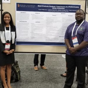 Two students standing in front of a research poster