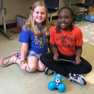 Two female STEM Campers interacting with technology