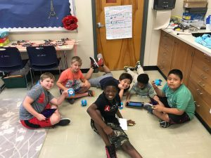 Large group of STEM campers interact with technology
