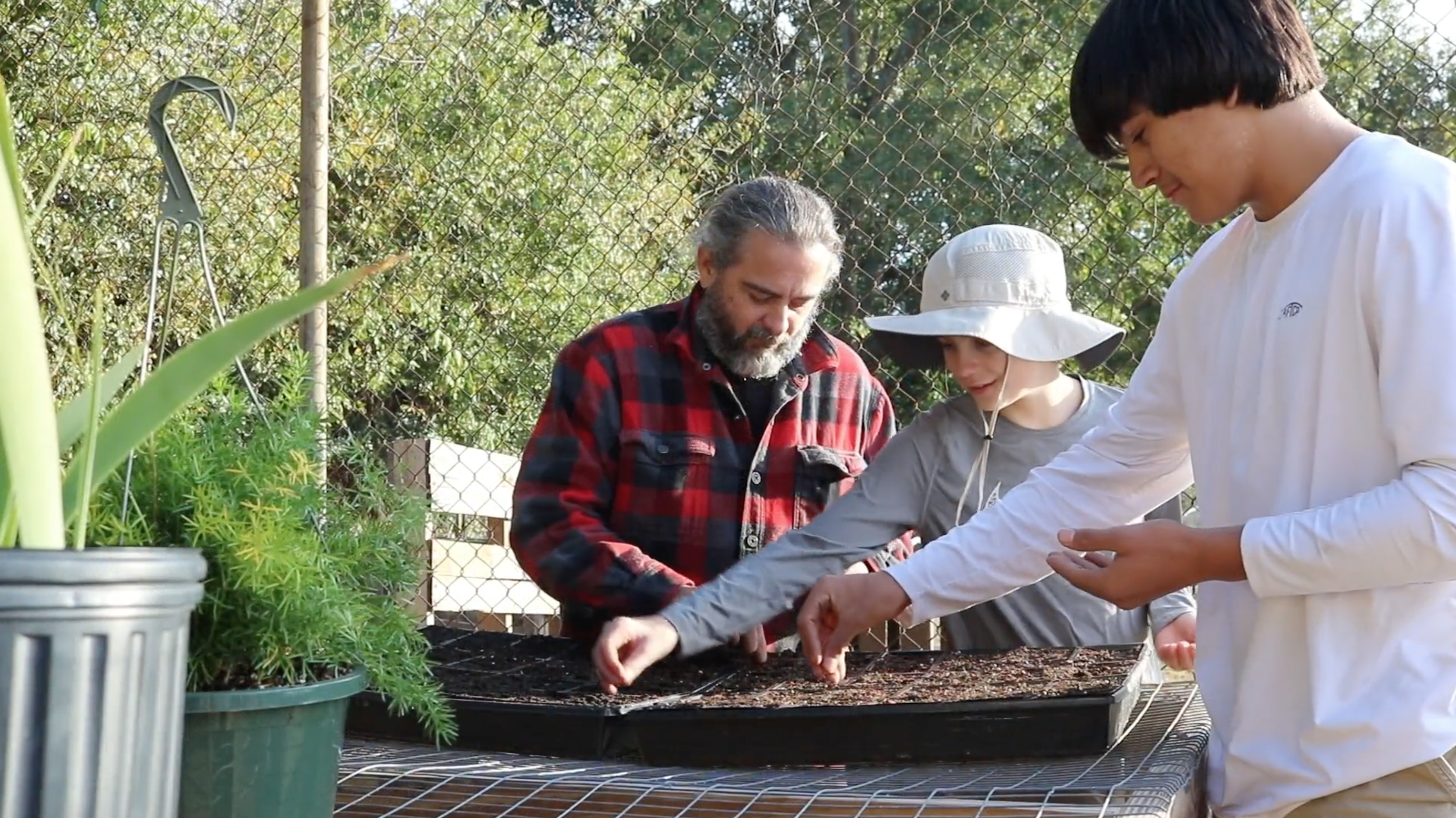 Dr. Forbes planting seeds with two volunteers