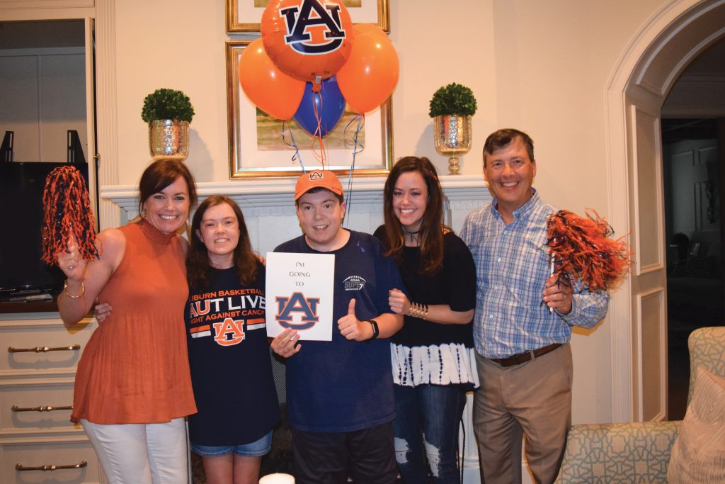 """Katie Basden and family with Bradley holding a sign saying """"I'm going to Auburn"""""""