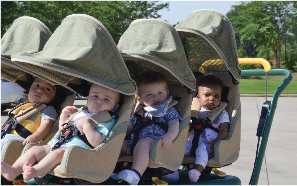 Infant students in a stroller that seats six