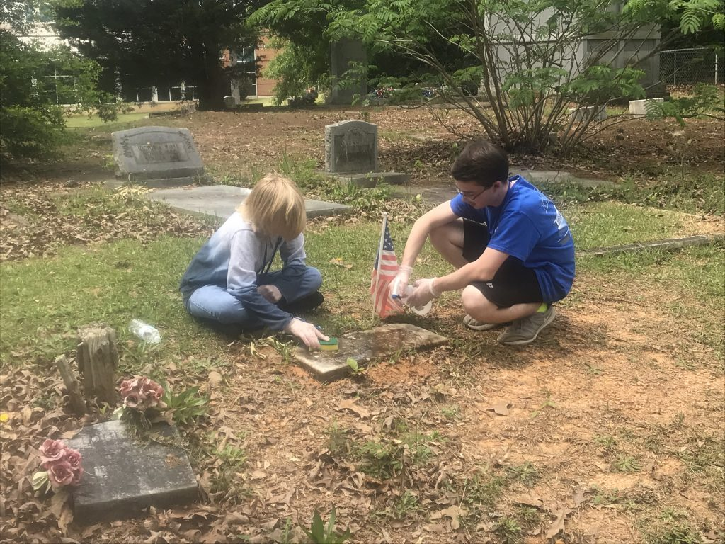 Two young students cleaning a gravestone