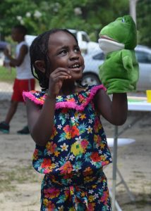 Little girl playing with frog puppet