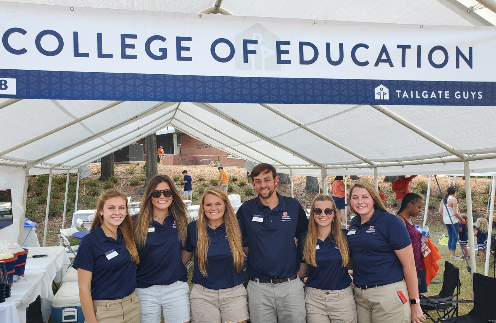 Student Ambassadors standing infront of the tailgate tent