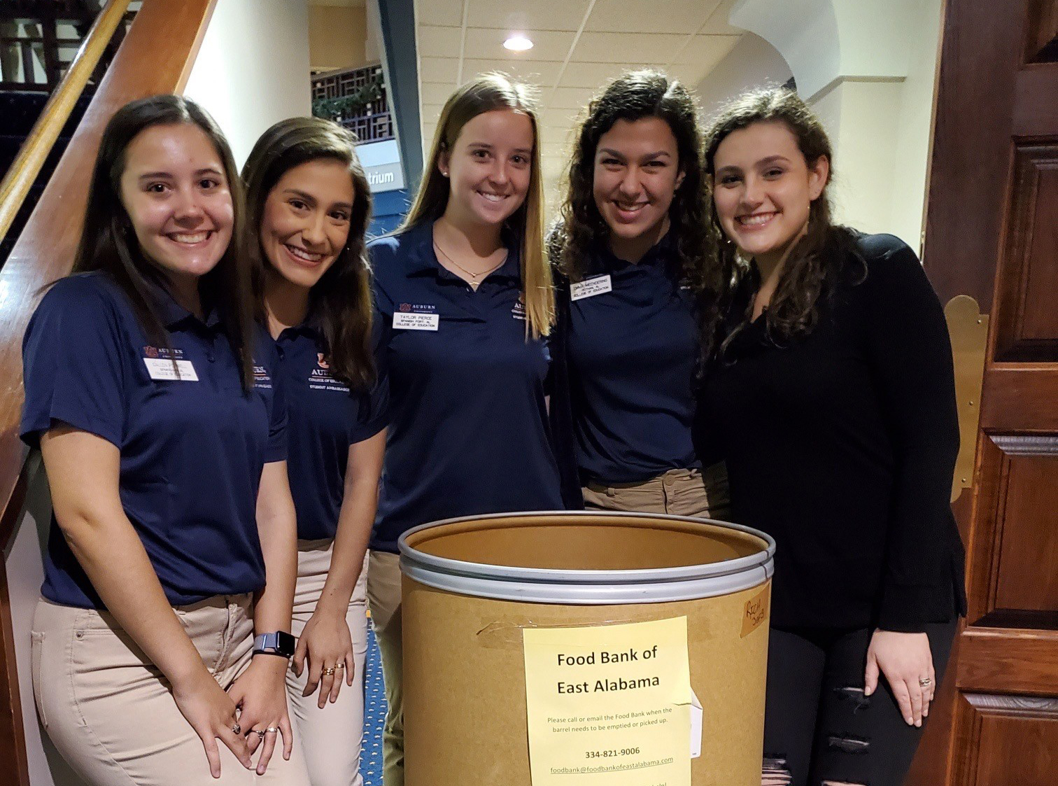 Student Ambassadors standing in front of the East Alabama Food bank can collector at Winter Wonderland