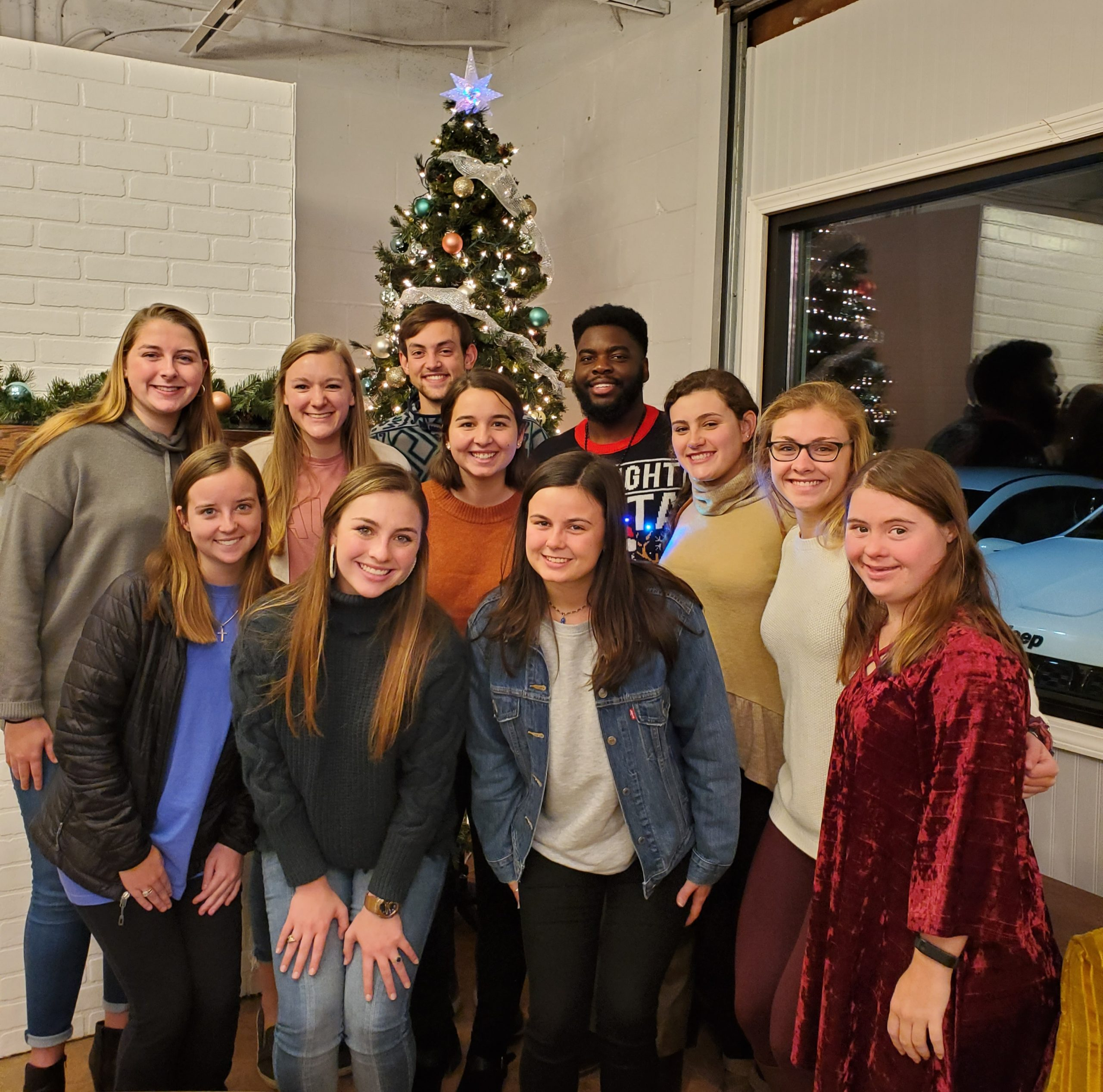 Student Ambassadors standing in front of a Christmas Tree
