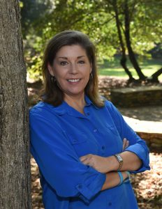 Tina Gottesman professional headshot outdoors leaning against a tree