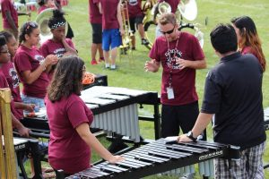 Justin Antos debriefing percussion instruments on football field