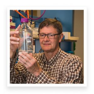 Bruce Gladden in Lab examining bottle with liquid