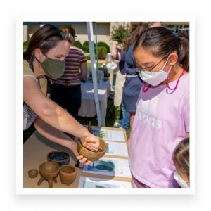 Christine Schnittka showing pottery to onlookers