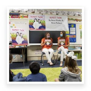 Anna Moates and Anna Penland reading to a classroom of students